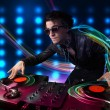 Stock Photo: Young Dj mixing records with colorful lights