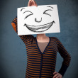 Woman with drawed smiley face on a paper in front of her head — Stock Photo #41595293