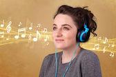 Mladá žena se sluchátky poslechu hudby — Stock fotografie
