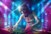 Dj girl mixing music in a club with blue and purple lights — Stock Photo