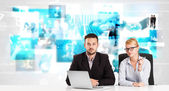 Business persons at desk with modern tech images at background — Photo