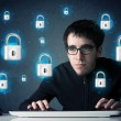 Stock Photo: Young hacker with virtual lock symbols and icons