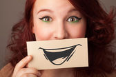 Happy cute girl holding paper with funny smiley drawing  — Stock Photo