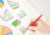Business person drawing colorful graphs and icons on paper — Stok fotoğraf
