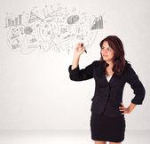 Söt flicka skissa grafer och diagram på vägg — Stockfoto