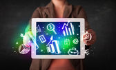 Young person holding tablet with graph and chart symbols — Stock Photo