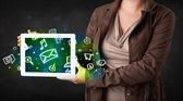 Person holding a tablet with media icons and symbols — Stock Photo