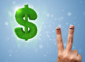 Happy smiley fingers looking at green leaf dollar sign — Stock Photo