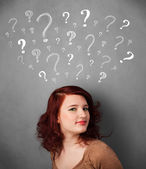 Young woman with question marks above her head — Stockfoto