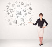 Young business woman presenting hand drawn media icons — Stock Photo