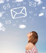 Young girl looking at mail symbol clouds on blue sky — Stock Photo