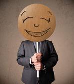 Empresário segurando uma placa de rosto sorridente — Foto Stock
