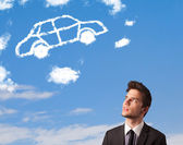 Handsome young man looking at car cloud on a blue sky — Stock fotografie