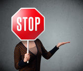 Young woman holding a stop sign — Стоковое фото