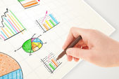 Business person drawing colorful graphs and icons on paper — Foto de Stock