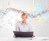 Business woman sitting at table with stock market graph  — Stock Photo