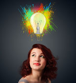 Young woman thinking with lightbulb above her head — Stock Photo