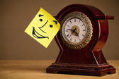 Post-it note avec visage souriant collée sur une horloge — Photo