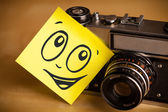 Post-it note with smiley face sticked on photo camera — Stockfoto