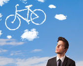 Young man looking at bicycle clouds on blue sky — Stock Photo