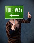 Giovane donna con un cartello di direzione — Foto Stock
