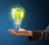 Glowing lightbulb in the hand of a woman — Stock Photo