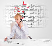 Business woman at desk with labyrinth and arrow — Stock Photo