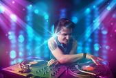 Dj miksowania muzyki w klubie z niebieski i fioletowy światła — Zdjęcie stockowe