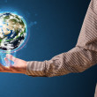 Businessman holding a glowing earth globe — Stock Photo