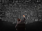 Businessman sitting in front of a blackboard with charts — Stock fotografie