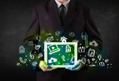 Person holding tablet with green media icons and symbols — Stock Photo