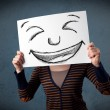 Woman with drawed smiley face on a paper in front of her head — Stock Photo
