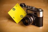 Post-it opmerking met smileygezicht gevezen op een fotocamera — Stockfoto