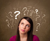 Girl with question mark symbols around her head — Stock Photo