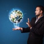 Businessman holding glowing earth globe — Stock Photo