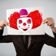 Businessman holding a cardboard with a clown on it in front of h — Stock Photo