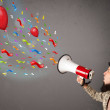Young guy having fun, shouting into megaphone with balloons — Stock Photo