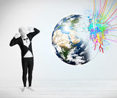 Funny man in body suit looking at colorful splatter earth — Stock Photo