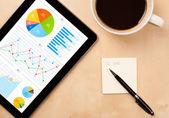 Tablet pc ile kahve masa üzerinde ekran grafikleri gösterir — Stok fotoğraf