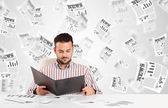 Business man at desk with stock market newspapers — Stock Photo