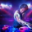 Disc jockey playing music with light beam effects on stage — Stock Photo #45893615