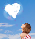 Cute girl looking at white heart cloud on blue sky — Stock Photo