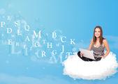 Dizüstü bilgisayar ile bulut içinde oturan genç kadın — Stok fotoğraf
