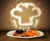 Delicious food plate with chef cook hat — Stock Photo