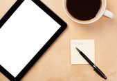 Tablet pc with empty space and a cup of coffee on a desk — Foto Stock