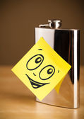 Post-it note with smiley face sticked on hip flask — Stock Photo