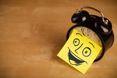 Nota post-it con cara sonriente sticked en reloj — Foto de Stock