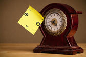 Post-it note with smiley face sticked on a clock — Stock Photo