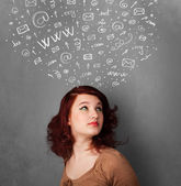Young woman thinking with social network icons above her head — Stock Photo