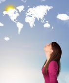 Young girl looking at world clouds and sun on blue sky — Stock Photo